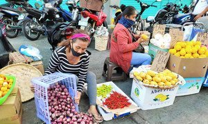 在菲律宾,从事非正规经济的人正面临着被新冠疫情影响而摧毁生计的危险。图为妇女在街边卖水果和蔬菜。