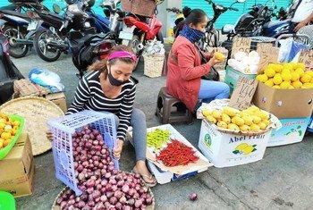 سيّدة تبيع الفاكهة والخضراوات على أحد الأرصفة في الفلبين، ويتعرّض العاملون في الاقتصاد غير الرسمي لخطر فقدان سبل كسب العيش بسبب جائحة كوفيد-19.