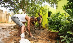 Workers in Bangalore, India, finish manually emptying a latrine pit.