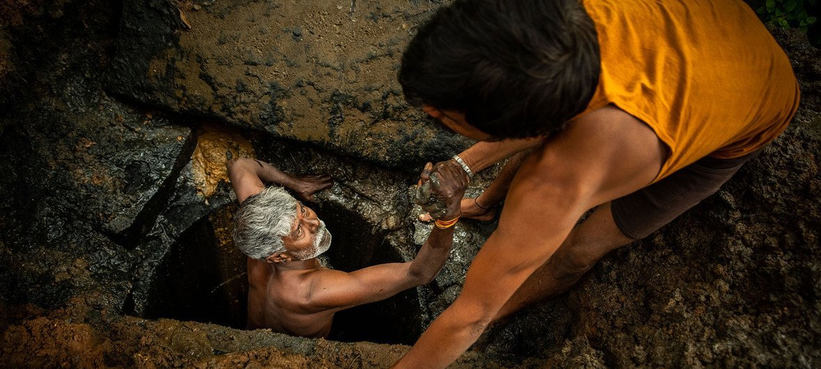 A latrine emptier is lifted out of a pit in Bangalore, India.
