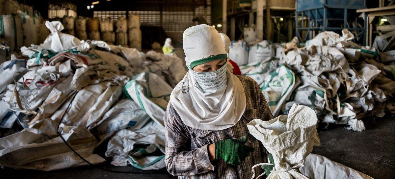 Trabajadora birmana empaca arroz en un molino de arroz en Tailandia