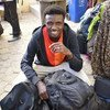 A quick smile from one of the 183 refugees resettled, originating in Sudan and the Central African Republic, prepares for his new life in France.