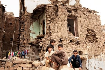 Children sit in front of a house damaged by an air strike in Yemen. (July 2019)
