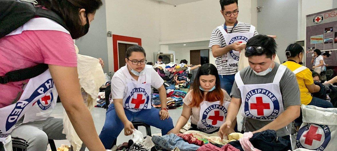 Estudantes voluntários no centro de logística da Cruz Vermelha para levar mercadorias de socorro às vítimas do vulcão Taal, nas Filipinas.