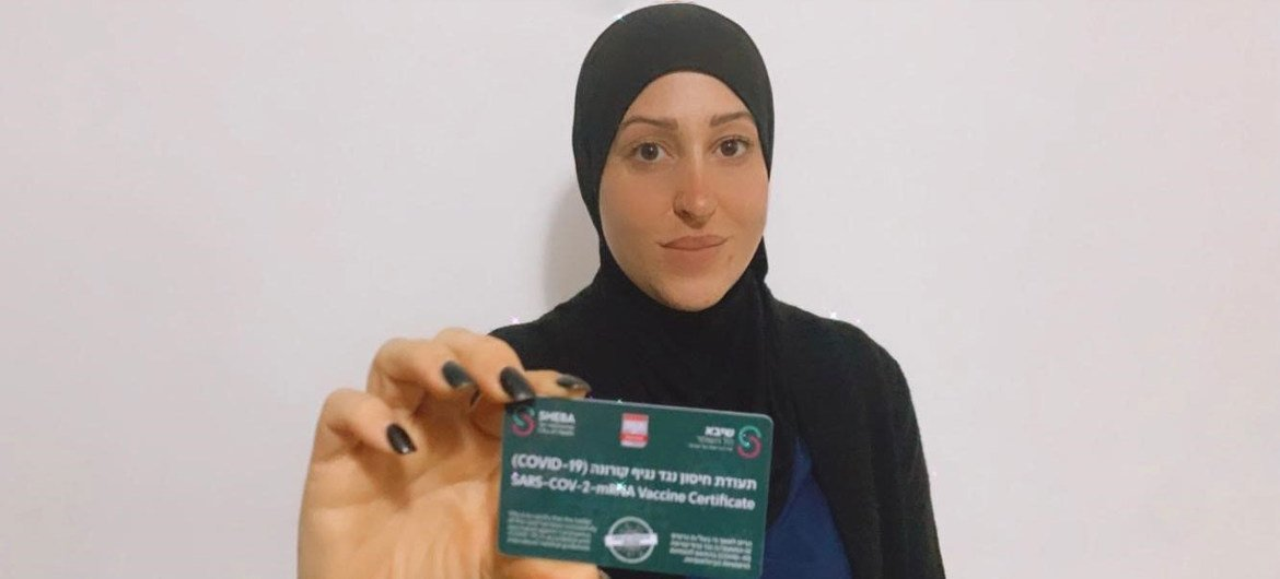An Arab-Israeli woman shows her COVID-19 card which shows she has been vaccinated against the virus.