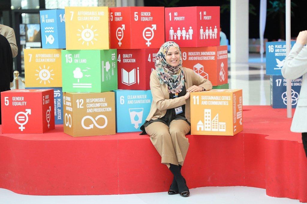 Une jeune femme assise devant les 17 Objectifs de développement durable. La question du financement du développement est plus que jamais importante alors que le monde répond à la pandémie de Covid-19 et doit préparer la reprise.