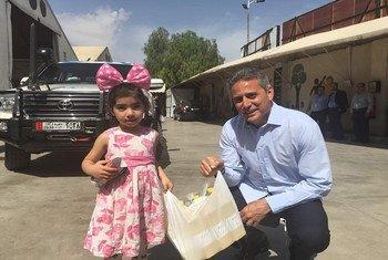 مهند هادي، المنسق الإقليمي للشؤون الإنسانية للأزمة السورية مع طفلة في دمشق قبل عدّة أعوام.