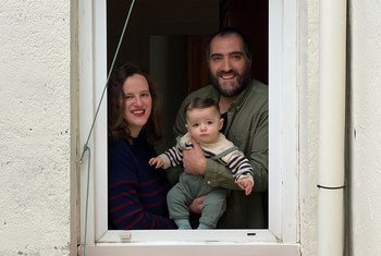 León, de 7 meses, y sus padres ven desde su casa el espectáculo de marionetas que hacen sus vecinos en Madrid, España