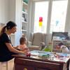 Escena de una familia en Madrid. Rubén, de 4 años, y su hermana pequeña juegan mientras su madre, Daniela, trabaja con su computadora..