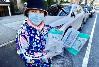 Membro da equipe das Nações Unidas mostra suprimentos médicos doados para combater a covid-19 na cidade de Nova Iorque.