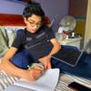 在纽约冠状病毒疫情暴发期间,这名十四岁的男孩在家中通过网络网上学,而他的父母进行远程办公。