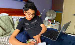 Fourteen-year-old boy attends school online from home while his parents telework during the Coronavirus outbreak in New York.
