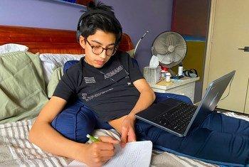 Un garçon de 14 ans va à l'école en ligne depuis chez lui tandis que ses parents font du télétravail pendant l'épidémie de coronavirus à New York.