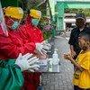 Des agents de santé montrent à un enfant comment se laver correctement les mains dans un centre de santé communautaire du centre de Java, en Indonésie.
