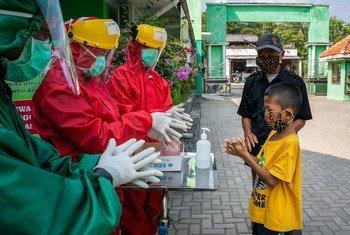 العاملون الصحيون يشرحون طريقة غسل اليدين بشكل صحيح لطفل في مركز صحي مجتمعي في وسط جافا، بإندونيسيا.