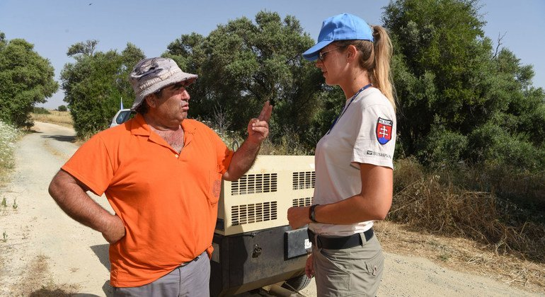A Slovak female UNPOL officer interacts with a farmer who works in the Cyprus buffer zone.