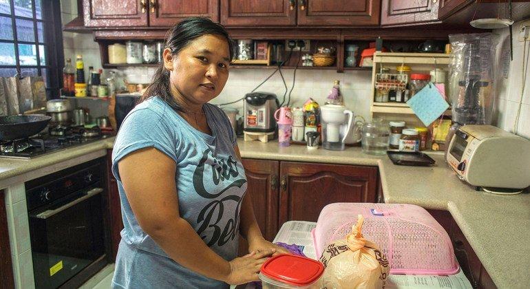 في سنغافورة، عاملة منزلية إندونيسية تعد الطعام في مطبخ رب العمل بعد رحلة الصباح الباكر إلى محل البقالة.