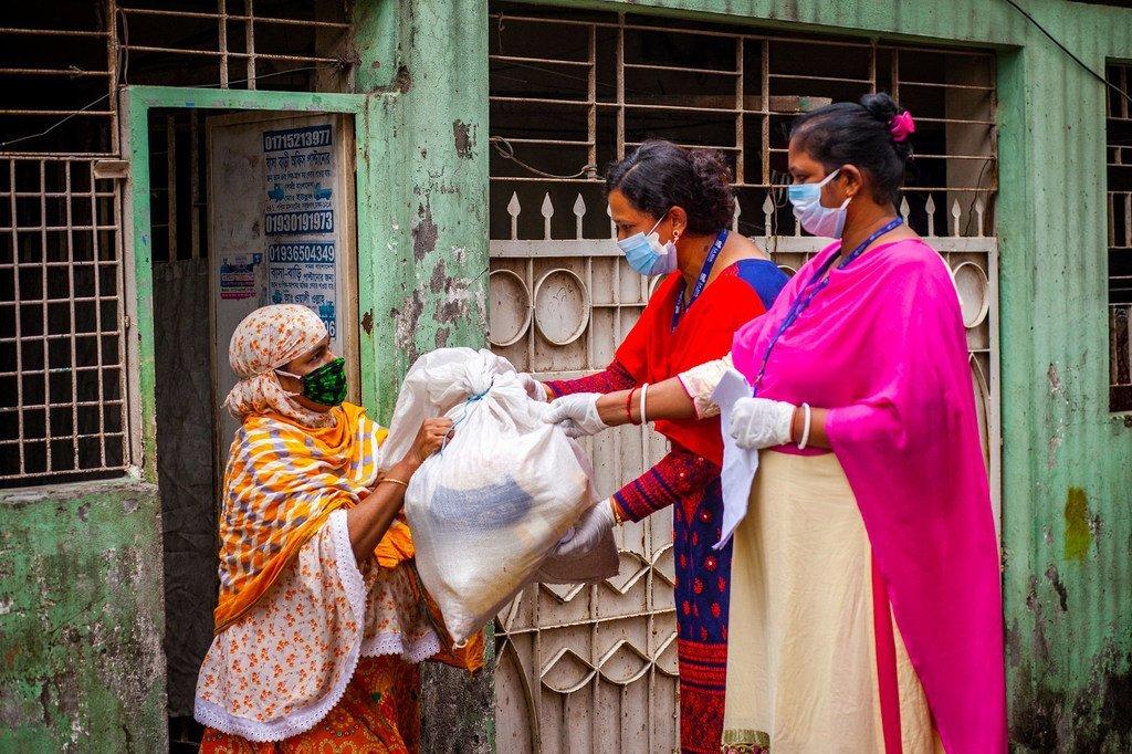在新冠大流行中,援助人员在孟加拉国达卡向一名妇女提供帮助。