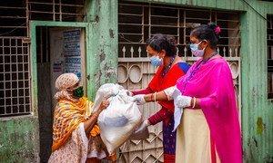 Trabajadoras de programas de desarrollo en Dhaka, Bangladesh, entregan asistencia a una mujer durante la pandemia de COVID-19.