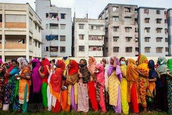Mulheres aguardando ajuda humanitária durante a pandemia de coronavírus em Dhaka, Bangladesh.