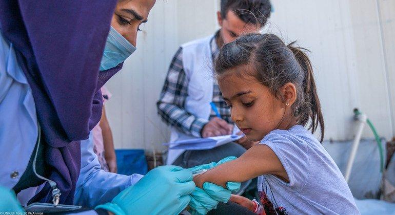 एक बच्ची, सीरिया के पूर्वोत्तर इलाक़े में संघर्ष से सुरक्षित बच निकलने के बाद, इराक़ में पोलियो और खसरा से बचाने वाले टीके लगवाते हुए.