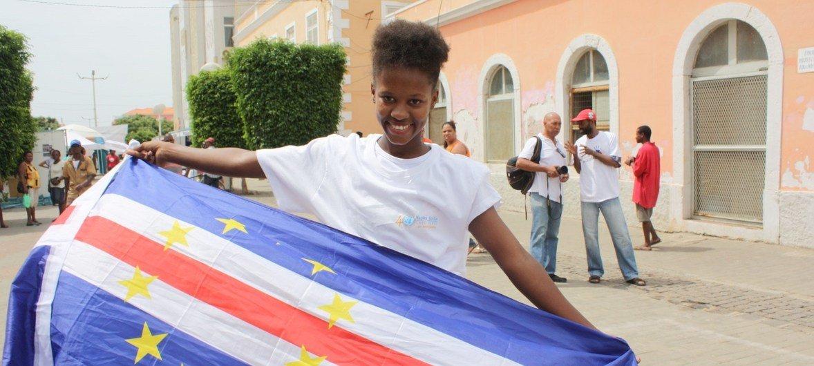 Jovem carrega bandeira de Cabo Verde na cidade da Praia.