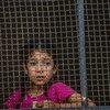 فتاة تنظر من وراء النافذة إلى عائلات نازحة وصلت من رأس العين إلى تل تامر، بعد أن فرت من العنف المتصاعد في سوريا (11تشرين الأول/أكتوبر 2019).
