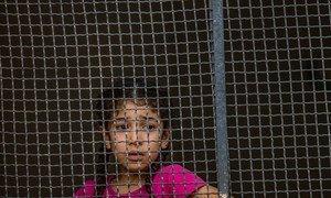 2019年10月11日,在叙利亚,一个女孩从一个安了金属网的窗子后面向外凝视。在窗子的里面,住着为了逃离了不断升级的暴力而从拉斯艾因(Ras al-Ain)颠沛流离来到了塔尔·塔默(Tal Tamer)的许多家庭。