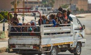 في 11 تشرين الأول/أكتوبر، نساء وأطفال يُنقلون على ظهر شاحنة من رأس العين إلى تل تامر، هربا من العنف في بلادهم سوريا.