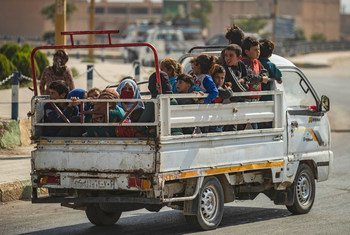 Na Síria, mulheres e crianças sendo transportadas na traseira de um caminhão, após fugirem da violência.
