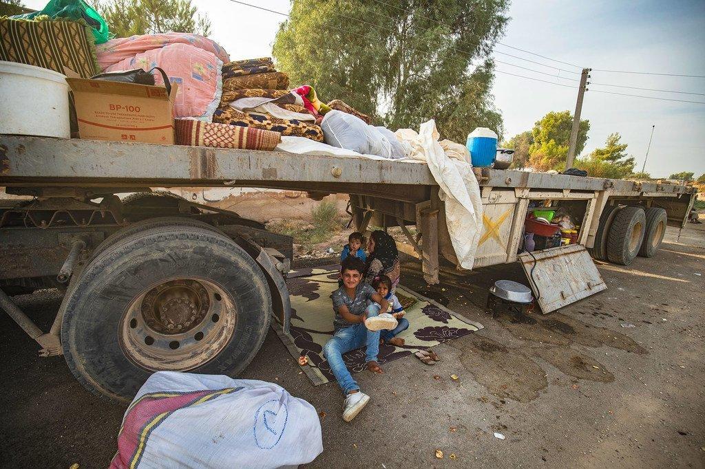 2019年10月11日,在阿拉伯叙利亚共和国,逃离不断升级的暴力的拉斯艾因流离失所者抵达塔尔塔梅尔时,一名妇女和儿童坐在一辆卡车下面。
