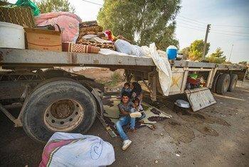 Em 11 de outubro de 2019, na Síria, mulher e crianças aguardam embaixo de um caminhão, em Tal Tamer, depois de fugir da escalada da violência.