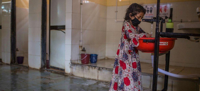 فتاة صغيرة تغسل يديها داخل أحد المرافق الخاصة بالنساء في مومباي بالهند.