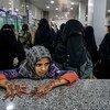 Recently displaced people wait to receive emergency aid in Marib, Yemen.