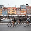 Tourists biking at Nyhavn in Copenhagen, Denmark.