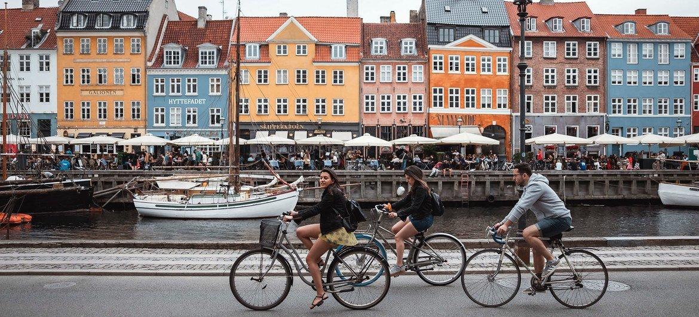 Des touristes font du vélo à Nyhavn à Copenhague, au Danemark.