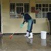 यूगाण्डा के एक स्वास्थ्य केन्द्र में एक कर्मचारी फ़र्श की सफ़ाई करते हुए. आबादियों को संक्रमणों और बीमारियों से बचाने के लिये साफ़-सफ़ाई और स्वच्छता बहुत ज़रूरी है.