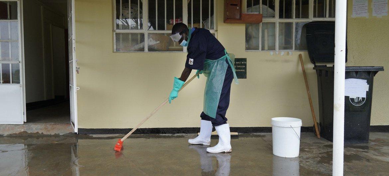 Un empleado de un centro de salud de Uganda limpiando el suelo con una mezcla de cloro y agua para prevenir infecciones.