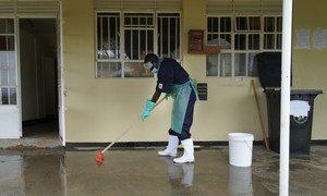 Funcionário de um centro de saúde em Uganda limpa o chão usando uma mistura de cloro e água para prevenir infecções. Serviços adequados de água, saneamento e higiene nas instalações de saúde são vitais para proteger as populações contra infecções.