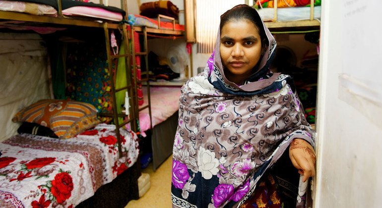 A Bangladeshi garment worker is seen standing in the room she shares with other seven colleagues in a factory dormitory in Jordan.