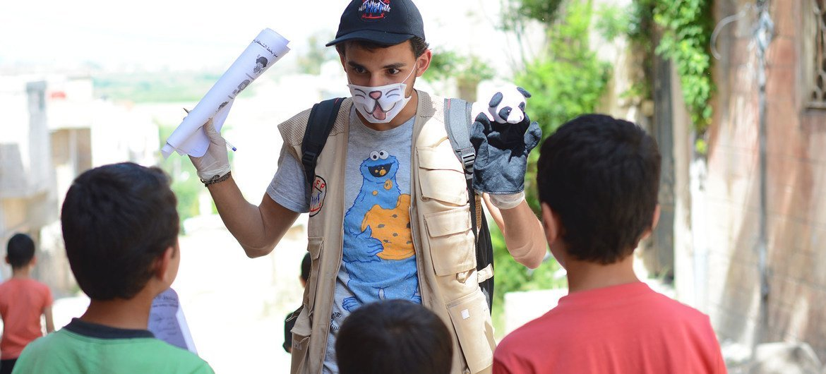 A young volunteer uses a hand puppet to educate children on COVID-19 awareness in northern rural Homs, Syria.