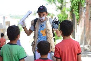 متطوع شاب يستخدم دمية لتثقيف الأطفال حول التوعية بمرض كوفيد-19 في ريف حمص الشمالي بسوريا.