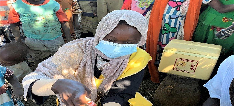 Un agent de santé administre à Munasa Muhyadin, deux ans, son vaccin contre la polio