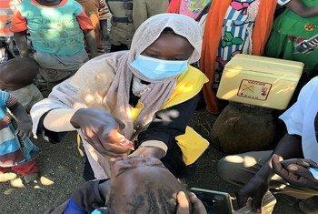 إحدى المُروَّجات لحملة التطعيم، أثناء إعطائها موناسا محيي الدين، ذات العامين، لقاح شلل الأطفال في غورلانغ بانغ، جنوب جبل مرَّة