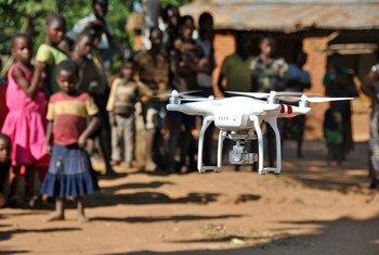 Crianças em aldeia do distrito de Kasungu, no Maláui, assistem a demonstração de drone