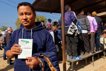 A Nepali construction worker receives his immigration documents which allow him to work in Saudi Arabia.