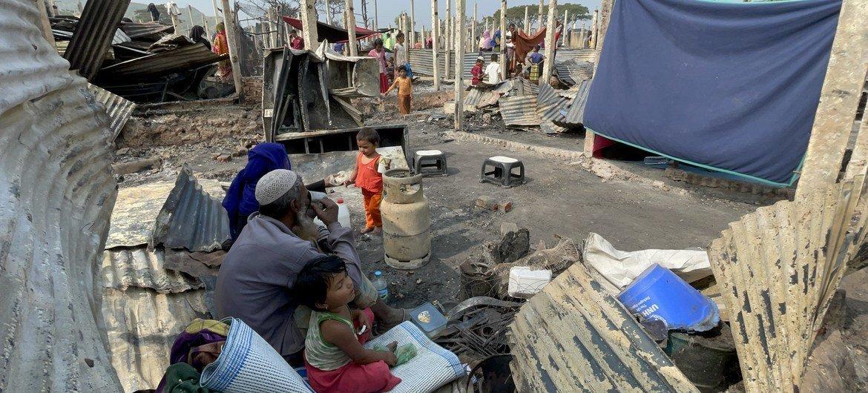 बांग्लादेश के नयापाड़ा शरणार्थी शिविर में विनाशकारी आग लगने के बाद, अपने शिविर के बचे-खुचे स्थल पर मौजूद एक रोहिंज्या शरणार्थी परिवार.
