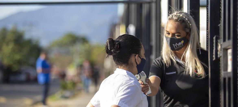 Una maestra le toma la temperatura a Keisy, una estudiante en la escuela Leon XIII, ublicada en el área de exclusión social en San José, la capital de Costa Rica, antes de entrar a la escuela.