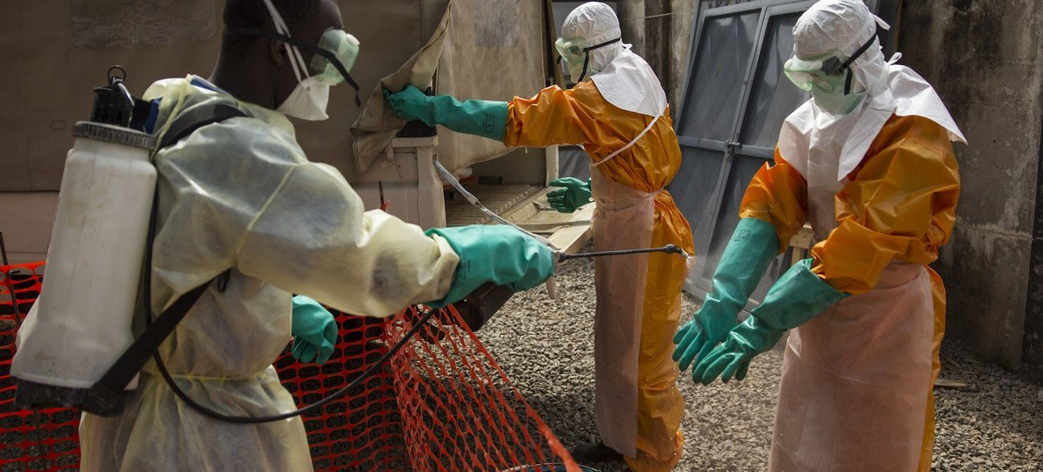 In this photograph from 2015, an IFRC worker sprays disinfecting chlorine solution on the gloved hands of a fellow worker in Conakry, Guinea. The country was one of the worst-affected in the 2014-2016 West Africa Ebola outbreak.