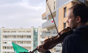 Aldo Sebastián Cicchini, a violinist at RAI orchestra plays on a balcony in Milan, Italy during the COVID-19.
